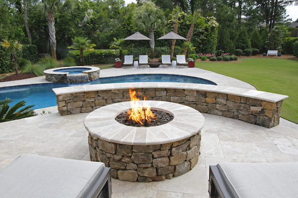 stone garden outdoor room fire-pit with seating wall, pool and spa, lounge chairs and umbrellas