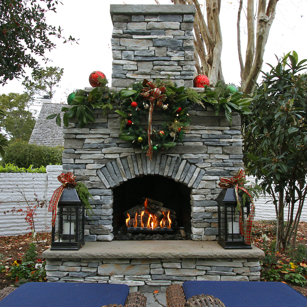 outdoor stone fireplace with Christmas decor and blazing fire