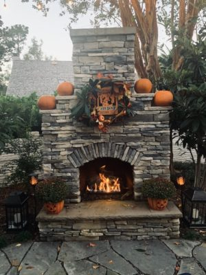 stone outdoor fireplace with Halloween Fall decor and blazing flames