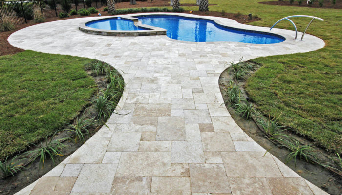 travertine stone tile pathway and swimming pool surround in garden