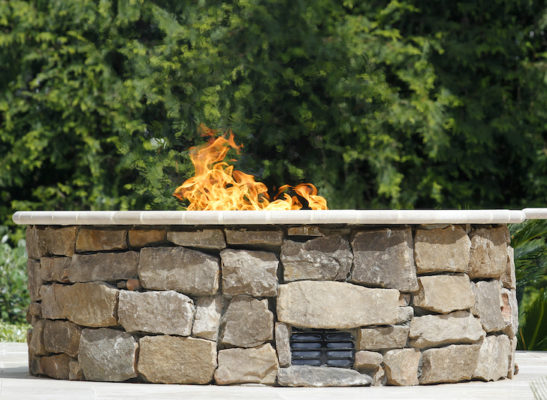 stone gas fire pit with flames on garden patio
