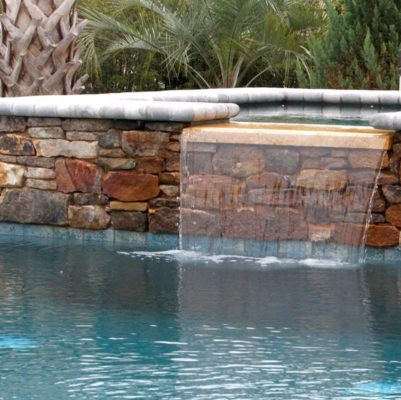 stone spa with waterfall into swimming pool in garden