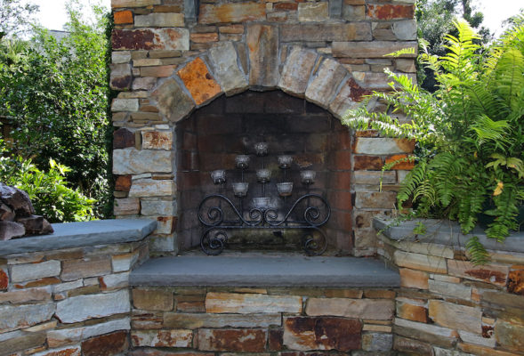 iron candelabra in an outdoor stone fireplace garden