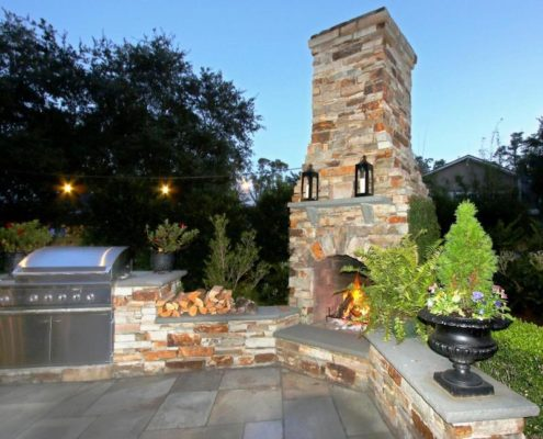 outdoor stone fireplace and grill on bluestone patio backyard