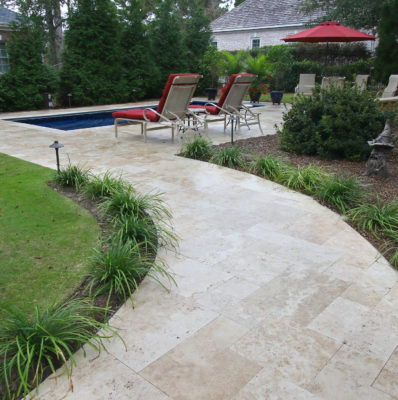 travertine stone tile pathway to pool and garden