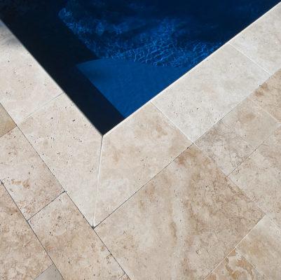 cream travertine stone tile corner by blue water in swimming pool
