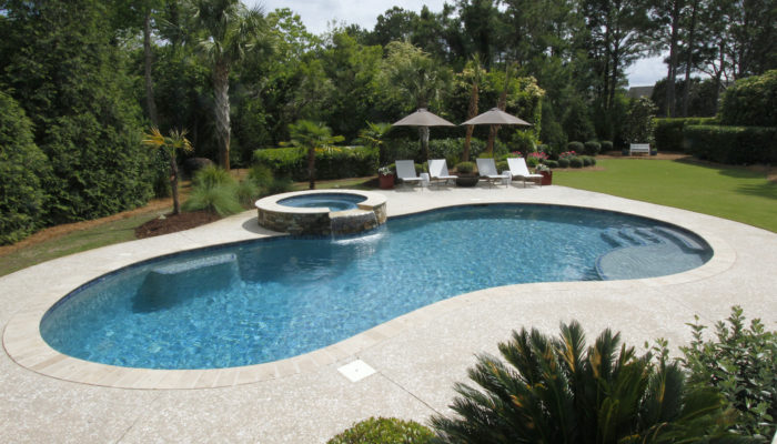 outdoor living room with swimming pool and spa, resort backyard, stone garden
