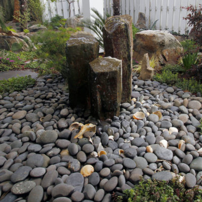 triple basalt column stone fountain on a bed of pebbles bubbling water in a garden