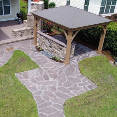 stone patio and grill station with gazebo and waterfall into pebbles garden