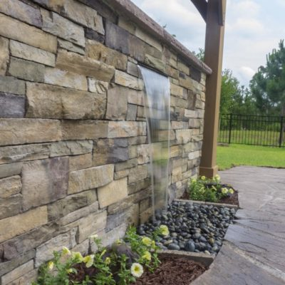 waterfall into pebbles on a stone grill cabinet in backyard garden