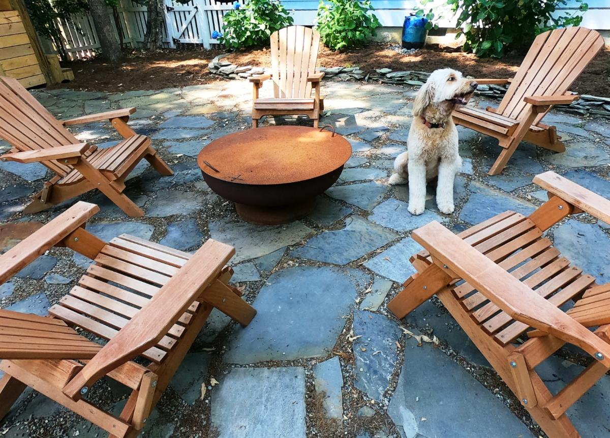 dog sitting on a flagstone patio by a fire bowl surrounded by Adirondack chairs