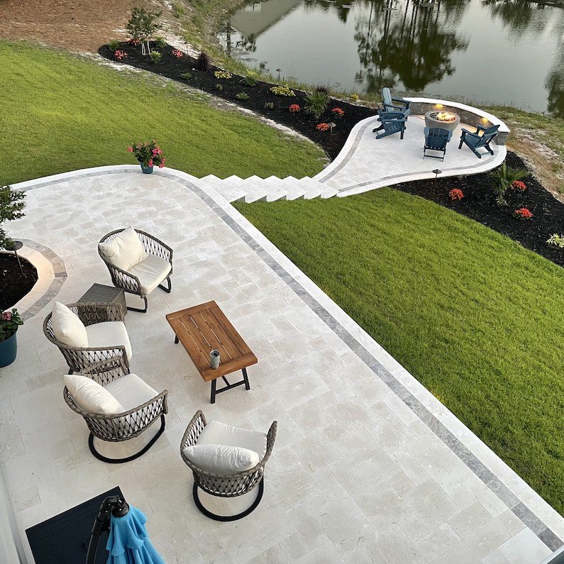 stone travertine tile backyard garden patio stairs and firepit area by a pond in wilmington north carolina